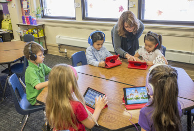 Caucasian teacher helping students use digital tablets
